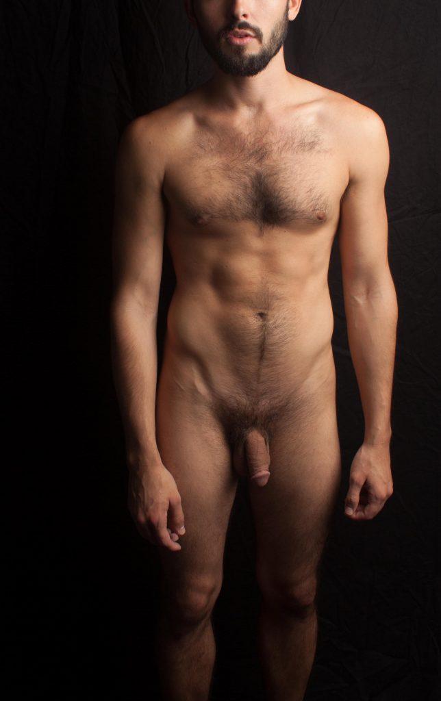 photo au naturel sur fond noir d'un homme nu au repos